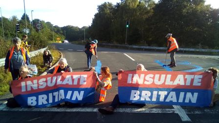 """Protestors sit down on a slip road holding """"Insulate Britain"""" banners"""