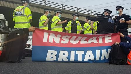 """Police behind an """"Insulate Britain"""" banner"""