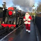 Santa Claus stands on the station of the North Yorkshire Moors Railway next to the Santa Express steam train