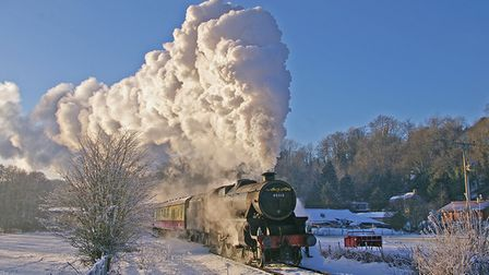 A NYMR steam train runs through a snow covered field in the North Yorkshire Moors