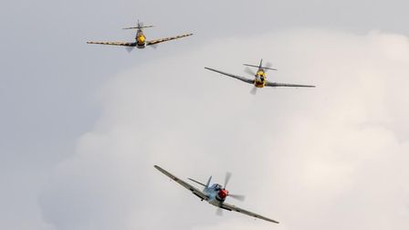 Three American aircraft, two Mustangs and a Thunderbolt, re-enacting a 'dogfight' in the air.
