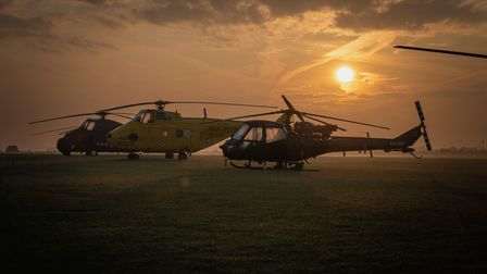 Historic Helicopters line up along the airside at sunrise, ahead of their flying display in the afternoon at IWM Duxford.
