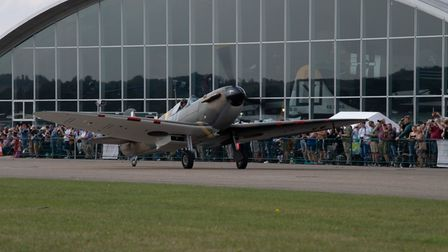 A Spitfire taxis along the runway, in front of IWM Duxford's American Air Museum
