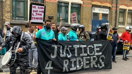 Food delivery couriers in Dalston and supporters stand with a sign demanding justice for riders.