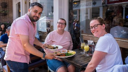 A waiter serves plates of food to customers at The Curious Goat, Saffron Walden