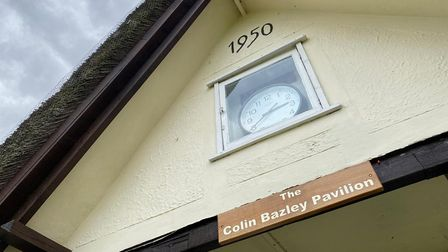 Cricket club pavilion with sign under the clock that reads: The Colin Bazley Pavilion. In Clavering, Essex