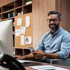 Smiling business man wearing eyeglasses working on desktop computer while using phone in office. Mid