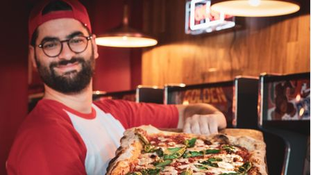 A man holds a metre-long pizza from Slice in Finsbury Park.