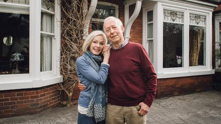 Senior couple are smiling for the camera while standing in front of their home.