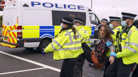 Police officers carry away a protester who had glued herself to a slip road at Junction 4 of the A1(