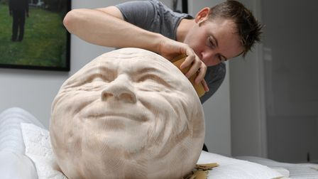 The artist sanding a head for the exhibition