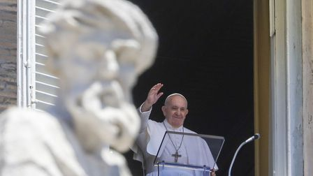 Pope Francis delivers his blessing as he recites the Angelus noon prayer from the window of his stud