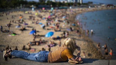 A woman smokes lying on a wall as people enjoy the beach in Barcelona, Spain
