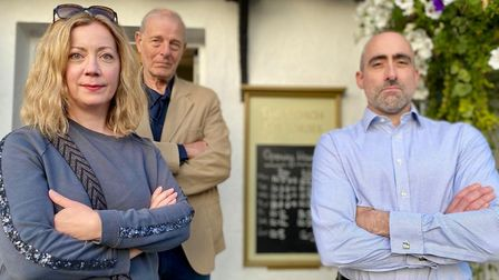 Three people stand with their arms folded outside the Coach and Horses pub in Newport, Essex