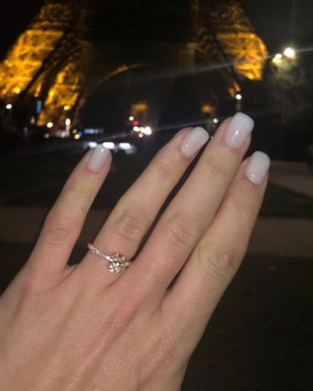 Kimberley Page shows off her new engagement ring in front of the Eiffel Tower