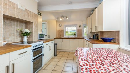 The kitchen is fitted with a range of country cream shaker-style fronted units