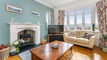 The sitting room with log-burning stove and oak flooring