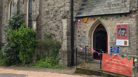 Grey church building on a sunny day with a red banner and bunting around the entrance