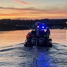 Sidmouth Lifeboat towing a boat at sunset across the water to Axmouth