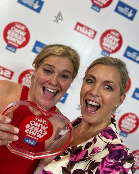 Two women - Annie Aris and Karen Shears - smile holding their The Sun Who Cares Wins award at The Roundhouse, Camden