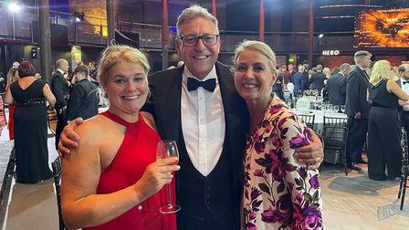 Three people - Annie Aris, Karen Shears and Nigel Railton, Camelot CEO - smile at the camera in The Roundhouse, Camden