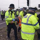 Police officers carry away a protester who had glued himself to a slip road at Junction 4 of the A1(