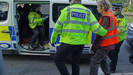 Officers lead a protester to a police van at a slip road at Junction 18 of the M25, near Rickmanswor