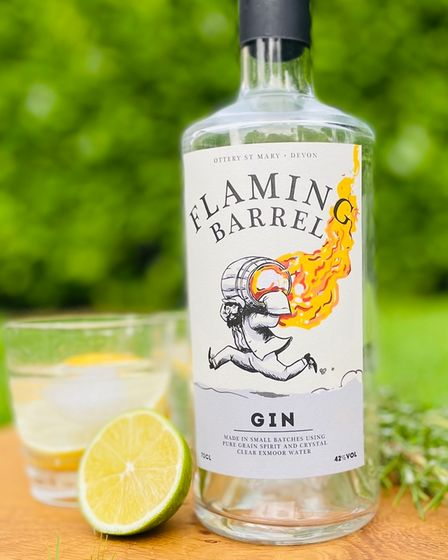 A clear bottle of gin with a label showing a man running with a flaming tar barrel