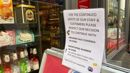 A sign outside Oh So Sweet asking customers to continue wearing masks