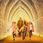 Family running through an archway of tiny golden lights