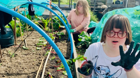 A girl who attends Mencap holds up a home-grown beetroot at the Dig It allotment in Saffron Walden