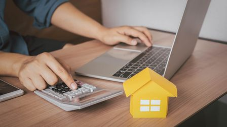 Person at a laptop with calculator and small model house