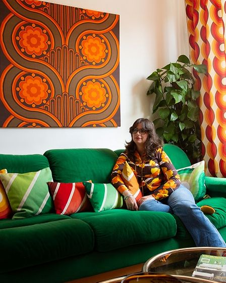 Estelle Bilson on a dark green sofa, with orange & brown curtains and artwork, wearing flares and a tunic top