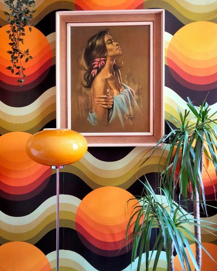 Wallpaper with dark brown background, then fawn, beige and cream waves and large bright orange balls