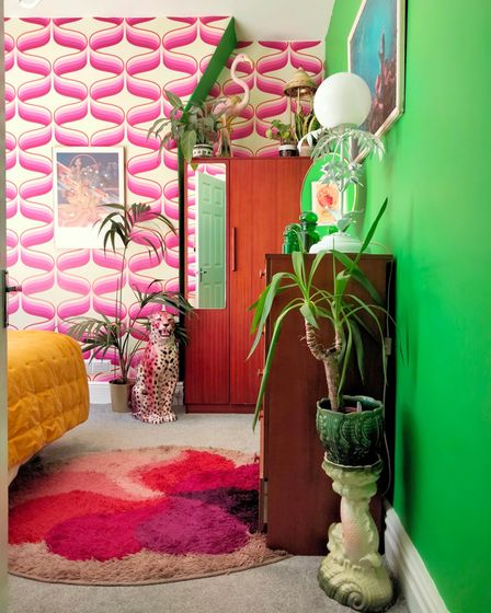 Bedroom with mustard bed topper, pink ripple wallpaper, bright green painted wall, swirly pink shagpile rug