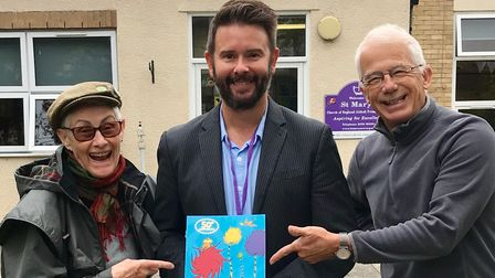 Three people - Trilby Roberts, Chris Jarmain and Edward Gildea - outside a Saffron Walden primary school with The Lorax book