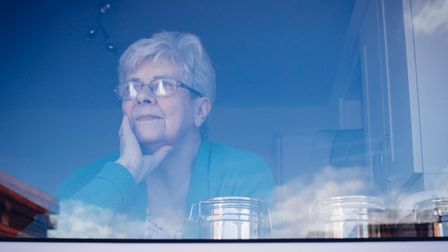 Senior woman looking out her kitchen window, deep in thought.