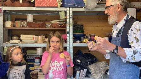 Rae Hayman demonstrates his pottery skills to Mollie and Anwen.