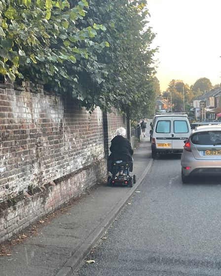 A woman on her mobility scooter on the narrow pavement where vans have been frequently passing