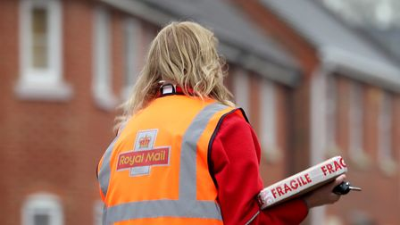 File photo dated 12/01/21 of A Royal Mail delivery worker in Ashford, Kent. Royal Mail has cautioned