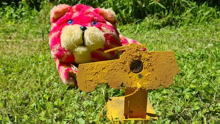 A Bagpuss toy behind a yellow air rifle target to depict the safety rule of awareness of what's behind the target