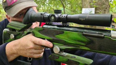 A man shooting a green air rifle in the woods holding his finger off the trigger, alongside it, for safety reasons