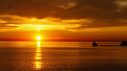 A fishing boat coming home at sunset