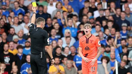 Brandon Williams of Norwich gets a yellow card from Referee David Coote during the Premier League ma