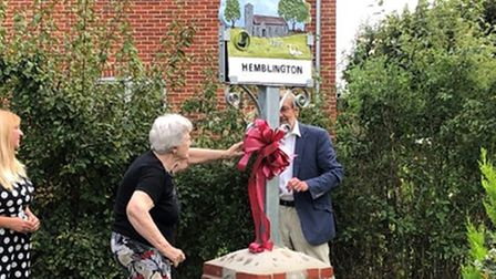 Ribbon cutting by Sue Smith, of Cutton's Corner, who was the winner of the original concept design competition for the sign