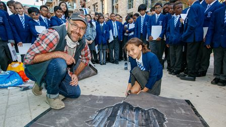 A pupil from St Edward's Primary with artist Joe Hill.