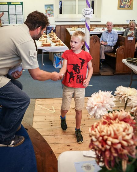 A boy is given an award at the Thaxted Gardening and Craft Show