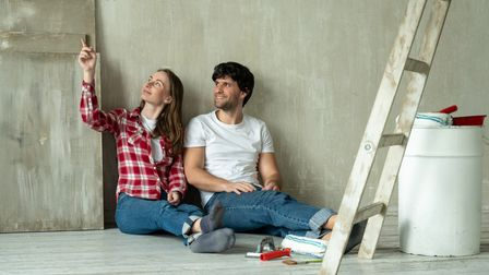 Happy family couple relaxing after painting. Young couple lying on the floor of new house and commun