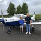 Henry Bean and instructor standing in front of the Piper Warrior he flew after winning an art competition