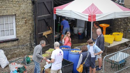 Volunteers on an apple pressing production line at The Railway Arms, Saffron Walden